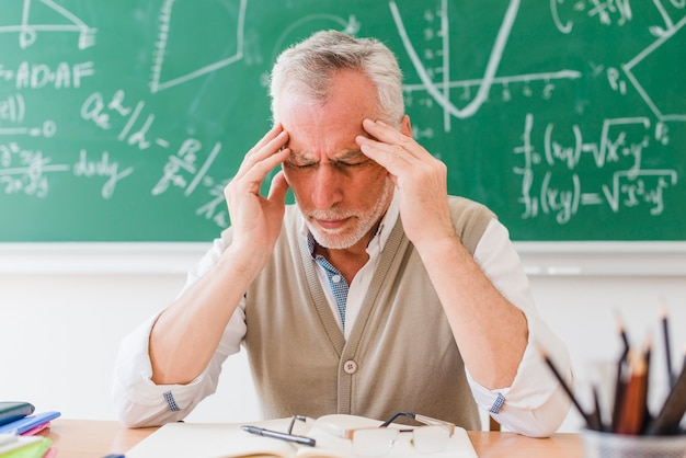 Stary nauczyciel z bólem głowy w sali wykładowej