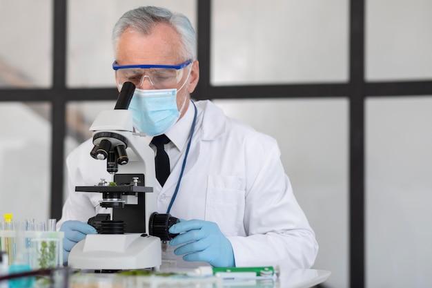 Stary naukowiec pracujący z mikroskopem