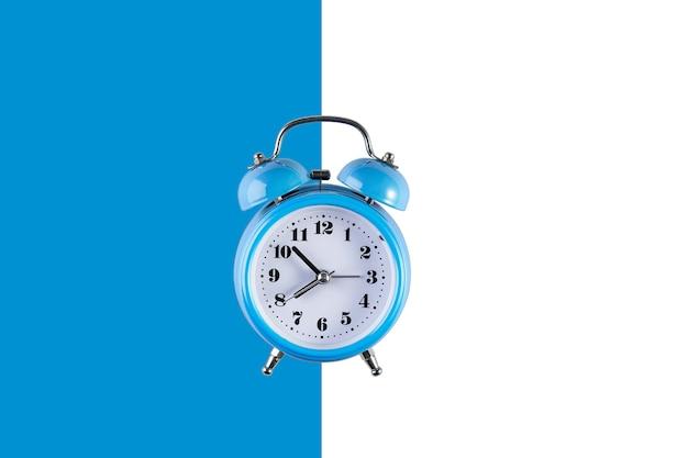 Stary niebieski budzik na niebiesko-białej ścianie. kreatywne mieszkanie leżał vintage zegar na kolorowej ścianie, kopiuj przestrzeń w minimalistycznym stylu, pusty szablon tekstu