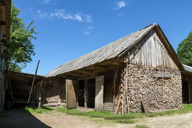 Stary nieociosany drewniany stajnia budynek w wiosce przy latem