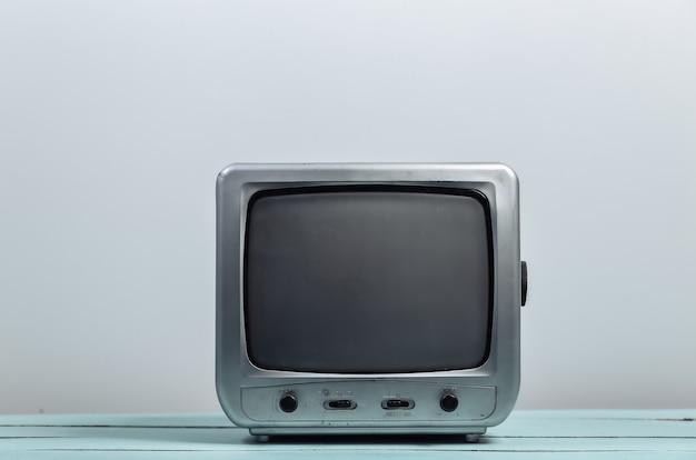 Stary odbiornik telewizyjny na białej ścianie. media retro