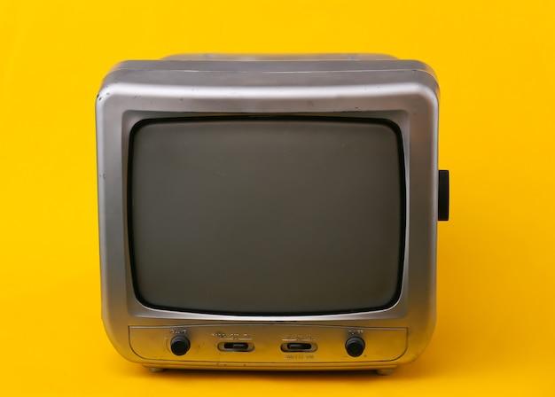 Stary odbiornik telewizyjny na żółto.