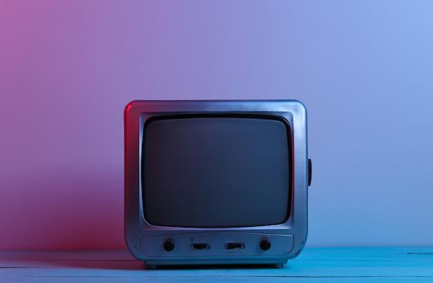 Stary odbiornik tv w czerwonym, niebieskim świetle neonowym. retro fala, media