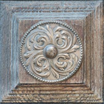 Stary odrapany okrąg z brązu z pięknym ornamentem na drewnianych drzwiach. zbliżenie