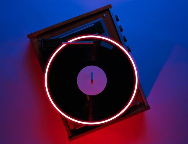 Stary odtwarzacz winylu. syntezatorowa fala i retrowave z lat 80-tych, świecące koło, futurystyczna estetyka