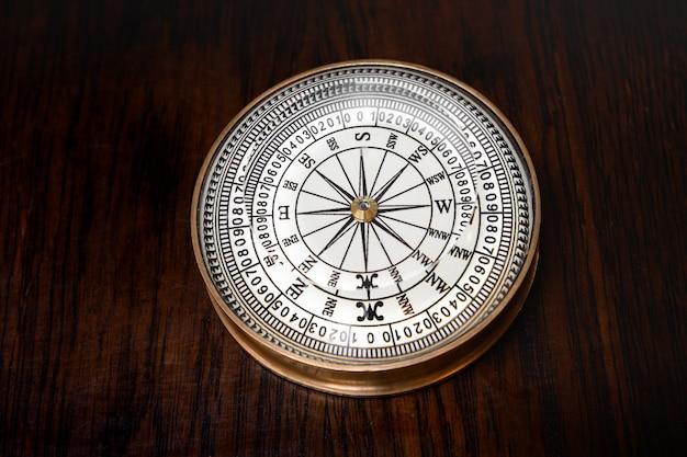 Stary okrągły mosiężny kompas magnetyczny ze szklaną tarczą leżącą na drewnianej desce