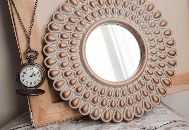 Stary okrągły zegar vintage na łańcuszku obok okrągłego lustra we wnętrzu