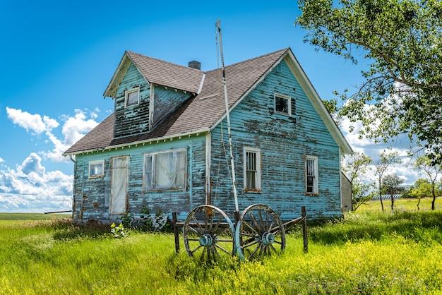 Stary, opuszczony dom wiejski z drzewami, trawą, błękitnym niebem i kołem wozu w kayville, saskatchewan, kanada