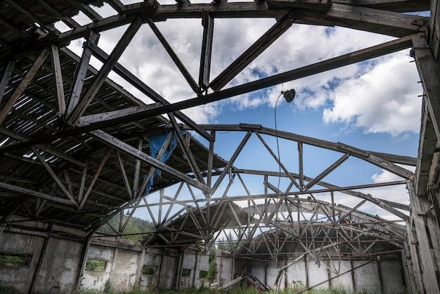 Stary opuszczony hangar magazynowy ze zrujnowanym, nieszczelnym dachem i drewnianą podłogą, porośnięty trawą w środku.