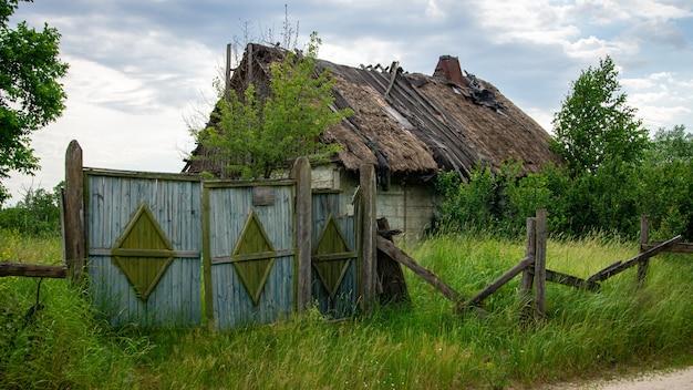 Stary opuszczony zrujnowany dom z dachem krytym strzechą i starą drewnianą bramą