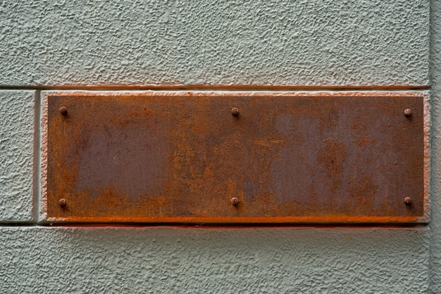 Stary ośniedziały metalu znak na ścianie.
