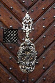 Stary ozdobny uchwyt brązowe drewniane drzwi. strzał zbliżeniowy