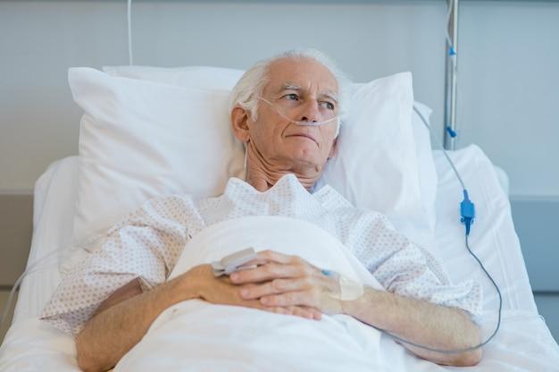 Stary pacjent leżąc na łóżku