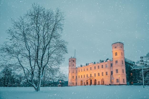 Stary pałac zimą jest oświetlony wieczorem. gatchina. rosja.