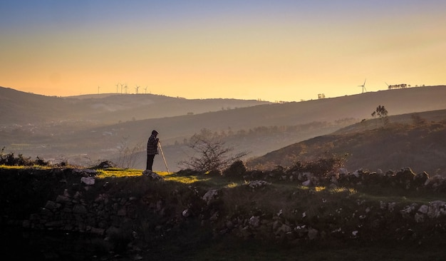 Stary pasterz patrząc w góry o zachodzie słońca