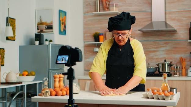 Stary piekarz nagrywa wideo kulinarne w kuchni przygotowując domową pizzę. emerytowany bloger, wpływowy szef kuchni, korzystający z technologii internetowej, komunikujący strzelanie, blogowanie w mediach społecznościowych za pomocą sprzętu cyfrowego
