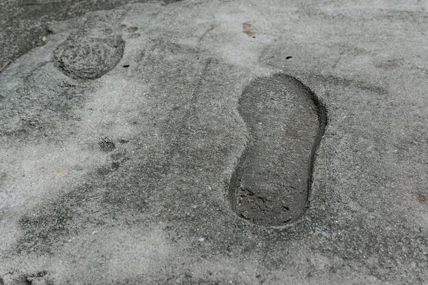 Stary pojedynczy odcisk, ślad buta lub buta na betonie