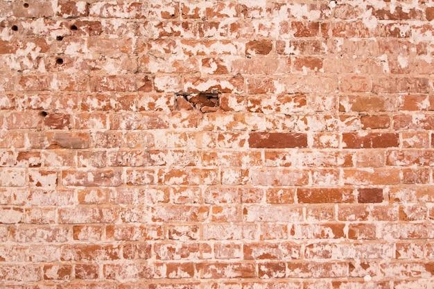 Stary pomarańczowy ściana z cegieł z pęknięciami na cegłach. odrapana ściana vintage