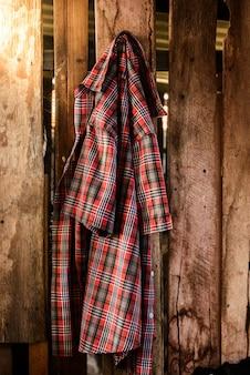 Stary pomarszczony szkockiej kraty koszula obwieszenie na drewnianym tle