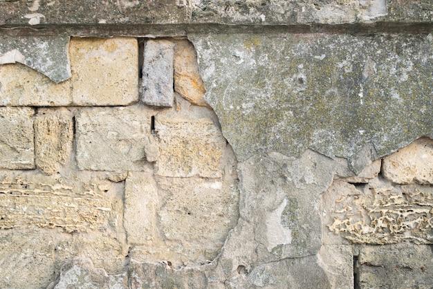 Stary popękany kamienny mur z zadrapaniami