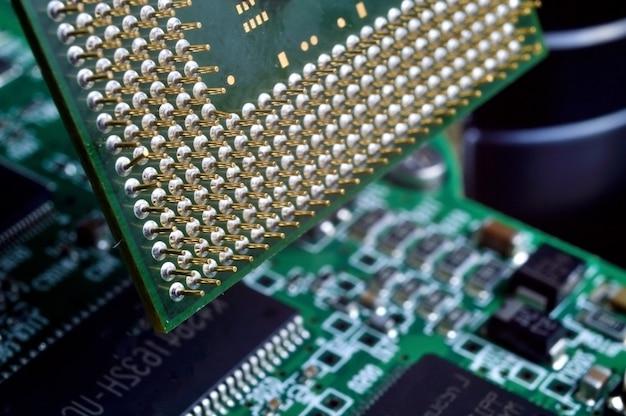 Stary procesor komputerowy z pozłacanymi nogami, mikroukładami na nim, zdjęcie super makro