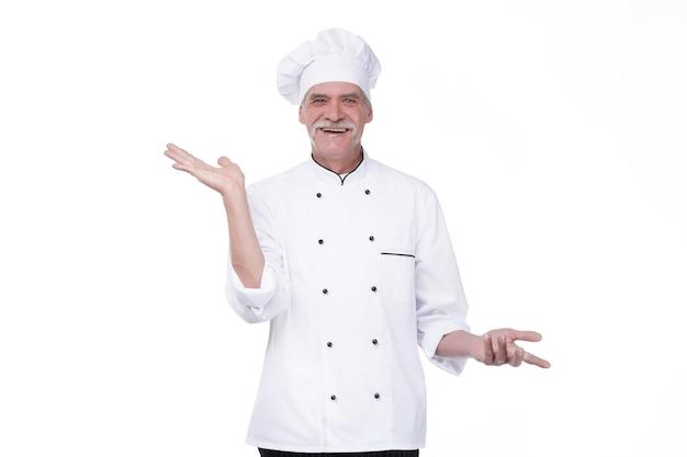 Stary profesjonalny kucharz na białym tle na białej ścianie, trzymając się za rękę