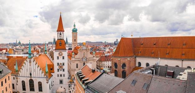Stary ratusz otoczony budynkami pod zachmurzonym niebem w ciągu dnia w monachium, niemcy