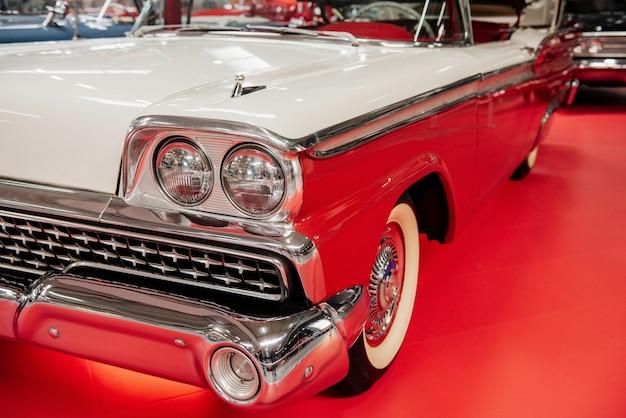 Stary retro biały kabriolet zaparkowany na czerwonej płytce na pokazie samochodowym