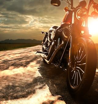 Stary retro motocykl podróżuje na wiejskiej drodze przeciw pięknemu światłu zmierzchu niebo