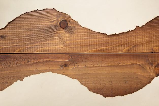Stary retro starzejący się papierowy pergamin na drewnianym tle