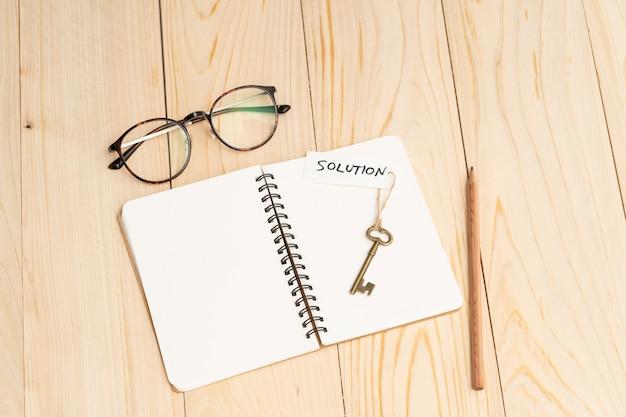 Stary rocznika klucz z rozwiązania słowem na pustym notatniku i czytelniczych szkłach