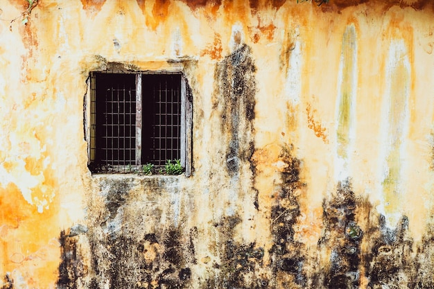 Stary rocznika okno domowy stary klasyk na żółtym wieśniaku malował betonowej ściany tło