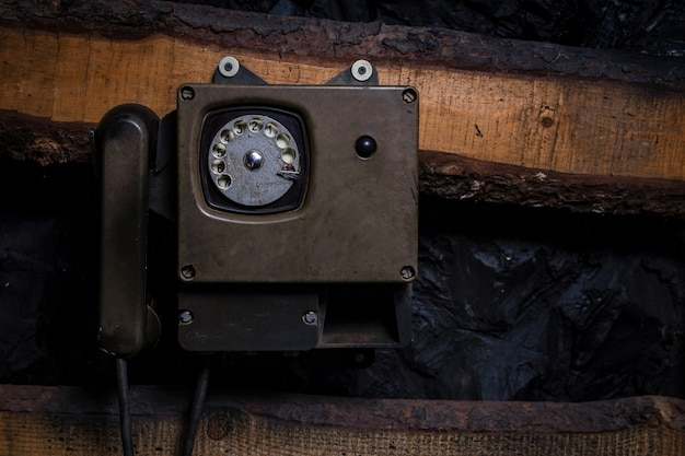 Stary rocznika sity telefon na starej drewnianej ścianie dla use w kopalni