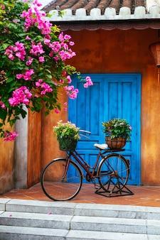 Stary rower z kwiatami w koszu na tle starej ściany. dekoracja domu w ogrodzie. stary rower przy ścianie w ogrodzie. wietnam