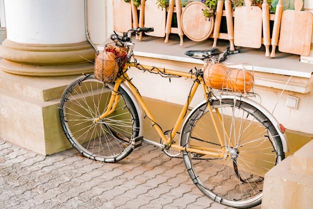 Stary rower z lampkami dyni i choinek stoi jako dekoracja w pobliżu budynku.
