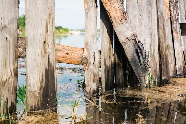 Stary rozbity drewniany płot zostaje zalany przez powódź na brzegu rzeki. katastrofa