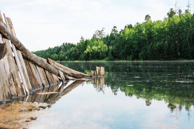 Stary rozbity drewniany płot zostaje zalany przez powódź na brzegu rzeki. klęska żywiołowa i zniszczenie. piękny krajobraz.