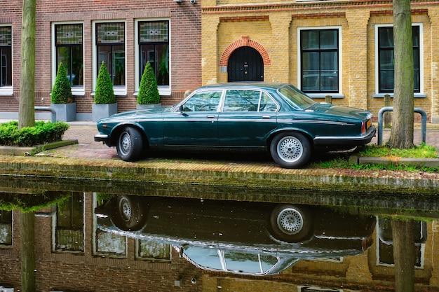 Stary samochód na nasypie kanału na ulicy delft delft w holandii