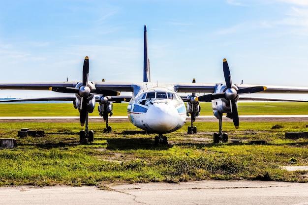 Stary samolot śmigłowy ładunku stoi na parkingu w pobliżu pasa startowego, obraz w tle