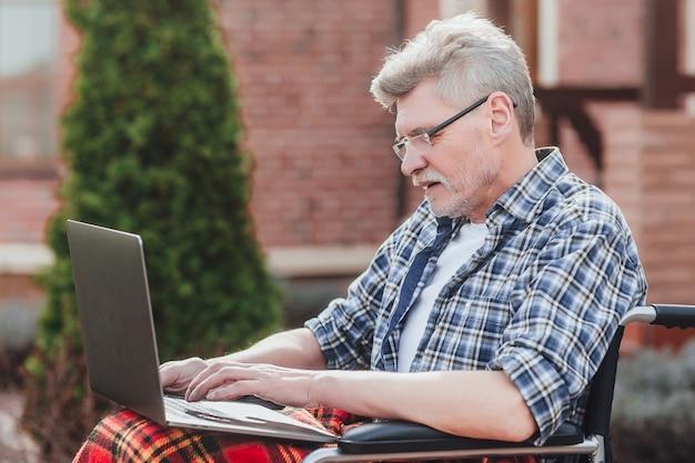 Stary siedzi na wózku inwalidzkim za pomocą laptopa blisko domu opieki