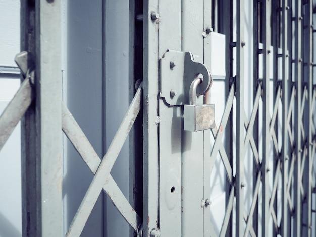 Stary srebrny zamek na żelaznych drzwiach przesuwnych.