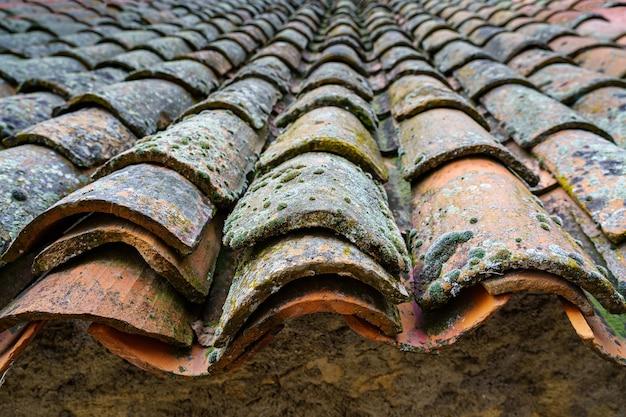 Stary średniowieczny dach domu z glinianych dachówek postarzanych z upływem czasu. hiszpania.
