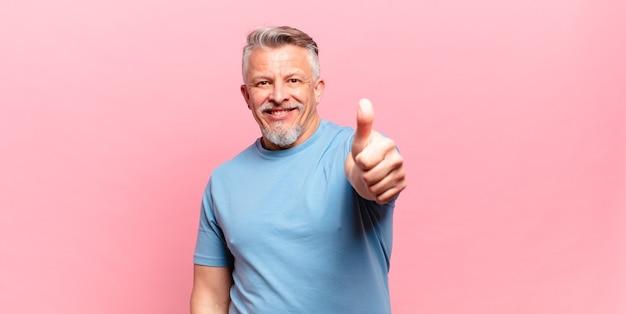 Stary starszy mężczyzna czuje się dumny, beztroski, pewny siebie i szczęśliwy, uśmiechając się pozytywnie z kciukami w górę