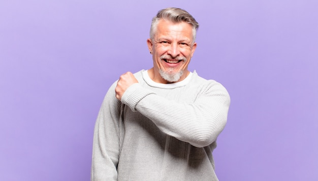 Stary starszy mężczyzna czuje się szczęśliwy, pozytywnie nastawiony i odnosi sukcesy, jest zmotywowany, gdy mierzy się z wyzwaniem lub świętuje dobre wyniki