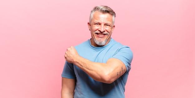 Stary starszy mężczyzna czuje się szczęśliwy, pozytywnie nastawiony i odnosi sukcesy, jest zmotywowany, gdy staje przed wyzwaniem lub świętuje dobre wyniki