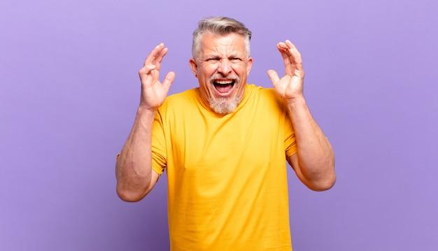 Stary starszy mężczyzna krzyczy z rękami w górze, czuje się wściekły, sfrustrowany, zestresowany i zdenerwowany