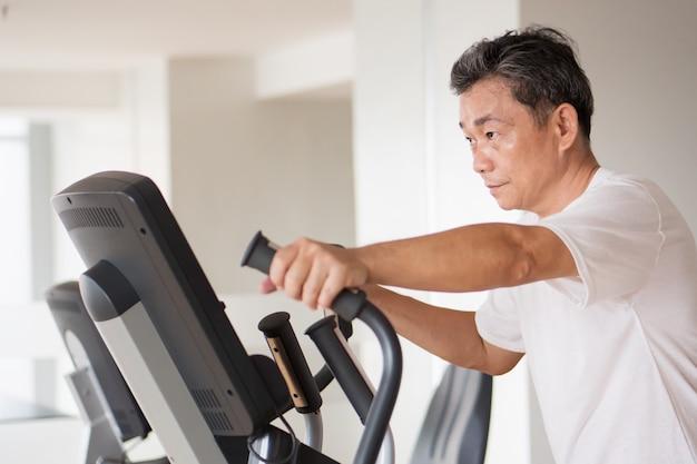 Stary starszy mężczyzna pracujący z nowoczesnym sprzętem fitness