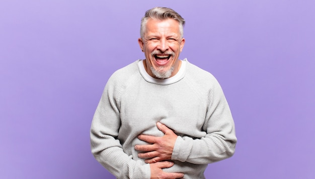 Stary starszy mężczyzna śmiejący się głośno z jakiegoś przezabawnego żartu, szczęśliwy i wesoły, dobrze się bawiący