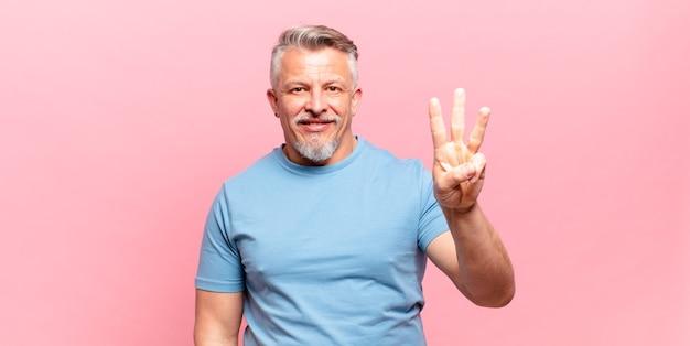 Stary starszy mężczyzna uśmiechający się i wyglądający przyjaźnie, pokazujący numer trzy lub trzeci z ręką do przodu, odliczający w dół