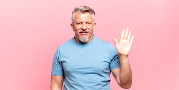Stary starszy mężczyzna uśmiechający się radośnie i radośnie, machający ręką, witający cię i pozdrawiający lub żegnający się